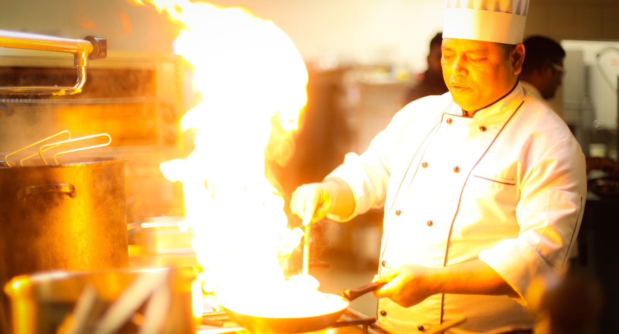A chef manages a large fire in his pan.
